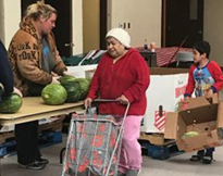 Volunteers helping to distribute produce to people in the community.